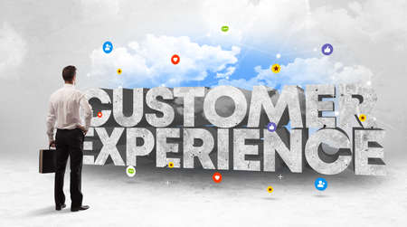 Young businessman standing in front of CUSTOMER EXPERIENCE inscription, social media concept
