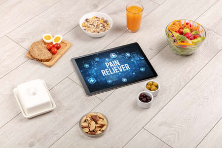 PAIN RELIEVER concept in tablet pc with healthy food around, top view