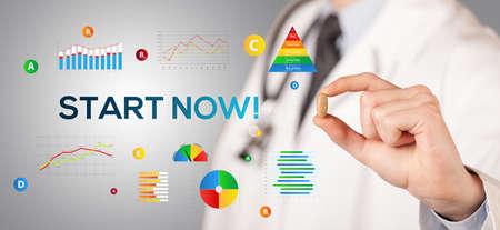 Nutritionist giving you a pill with START NOW! inscription, healthy lifestyle concept