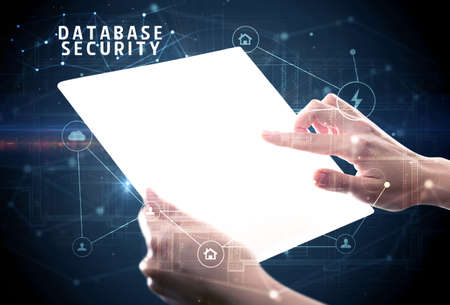 Holding futuristic tablet with DATABASE SECURITY inscription, cyber security concept