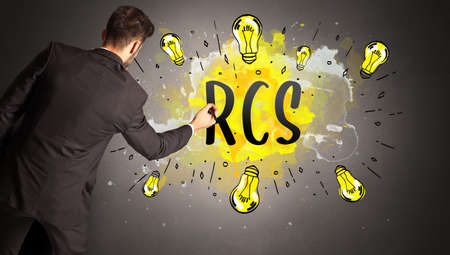 businessman drawing colorful light bulb with RCS abbreviation, new technology idea concept