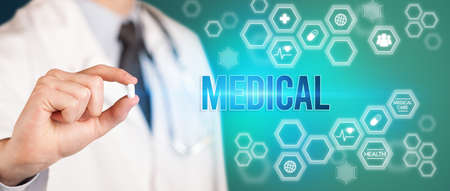 Close-up of a doctor giving you a pill with MEDICAL inscription, medical concept