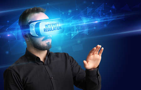 Businessman looking through Virtual Reality glasses, virtual security concept Foto de archivo