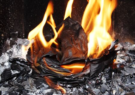 walling: Tongues of flame on burning sheets of paper in a fireplace fire chamber. Stock Photo