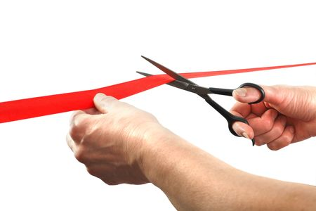 cutting through: Scissors cutting through red ribbon or tape, isolated on white. Scissors cutting ceremony Stock Photo