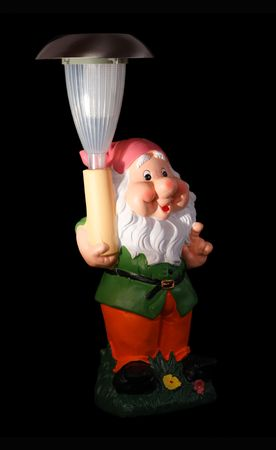 Decorative Garden Gnome with the Solar Light. Isolated object on a black background. photo