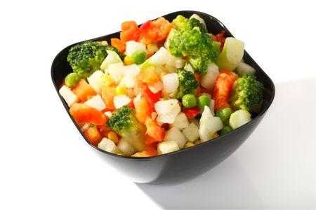 얼음 결정과 서리가 흰 배경에 스틸 컵에 냉동 야채