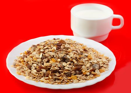 Muesli on a white plate and milk in a cup on a red background photo