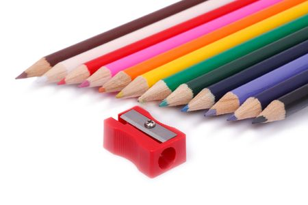 Red pencil Sharpener and Multi Colored crayons a white background. photo