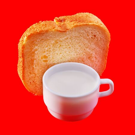 Milk in a cup and wheat bread on red. photo
