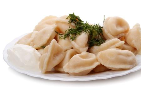 Nourriture russe traditionnelle - pelmeni (raviolis chinois). Pelmeni de Sib�rie avec viande, cr�me sure et aneth vert dans une plaque blanche. Banque d'images - 9866157