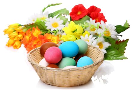 Easter eggs in a wicker basket and flowers isolated on white background photo