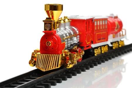 Tren en miniatura en la pista aislada sobre un fondo blanco