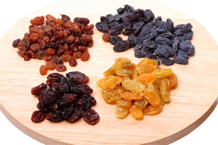 Four variety of raisins on a cutting board isolated on white background photo