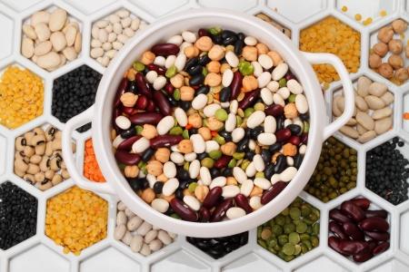 Varios productos de bean en celdas celulares en seco y mezclan en un cuenco blanco