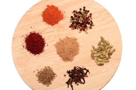 sumy: Seven spices (pepper, adjika, Sumy, cardamom, cloves, Zira, cinnamon, salt and herbs) on a round cutting board. Isolated on white background