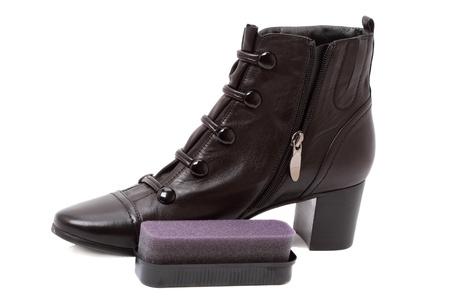 Black womens boot and a sponge shoe polish isolated on white background photo