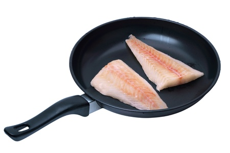 Frozen fish fillets in a skillet. Isolated on white background photo