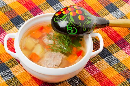 Soup in a white bowl and wooden spoon. Russian Culture photo