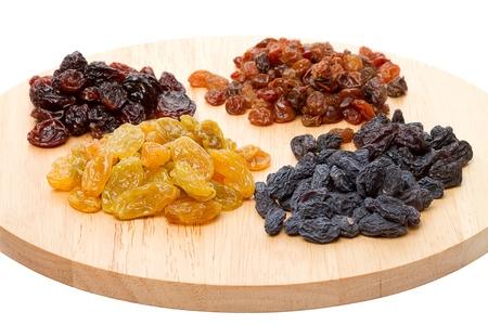 frutas secas: Cuatro variedad de uvas pasas en la tabla de cortar