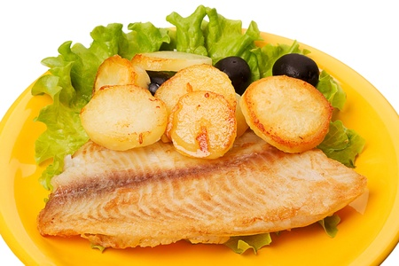 tilapia: Tilapia with roasted potatoes and olives on a yellow plate Stock Photo
