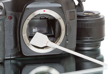 Cleaning digital SLR camera sensor with swab. White background.