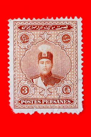 shah: Old Iranian postage stamp with a picture of Shah Ahmed, 1923  Red background  Stock Photo