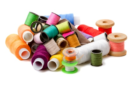 Heap spools of sewing threads isolated on a white background