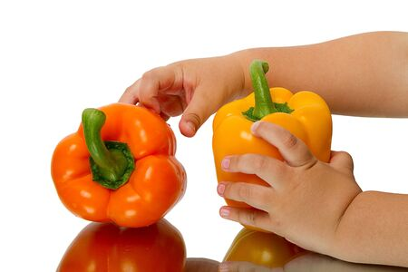Fresh sweet peppers and the hand of a child isolated on white background Stock Photo - 13728179