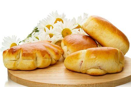 prodotti da forno: Prodotti da forno su un tagliere e margherite. Isolato su sfondo bianco Archivio Fotografico