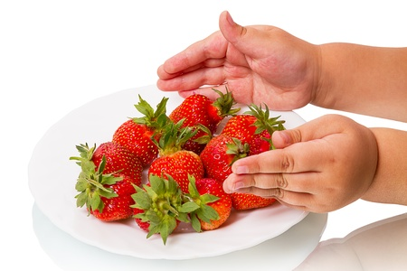 Childs hand reach for a plate with fresh strawberries  photo