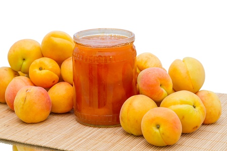 Heap apricots and a glass jar with apricot jam photo
