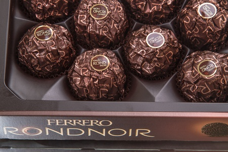 Tambov, Russian Federation - August 19, 2012: Box of chocolates Ferrero Rondnoir, candy coated with dark chocolate filled with cocoa cream and almonds. Production Ferrero S.p.A. Italy