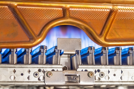 Blue flames of a gas burner inside of a boiler Stock Photo