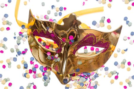 Golden carnival mask  and confetti isolated on white background photo
