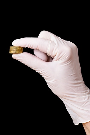 Hand in surgical gloves with five coins. Isolated on a black background photo