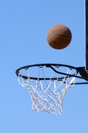 Basketball hoop and ball flying outdoors photo