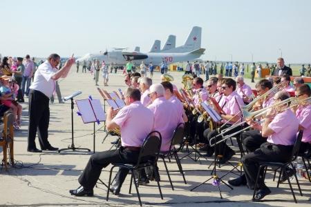 performs: Tambov, Russian Federation - 1 giugno 2013: tradizionale manifestazione aerea a Tambov. L'orchestra esegue la musica di strumenti a fiato in un aeroporto militare. Soleggiata giornata estiva
