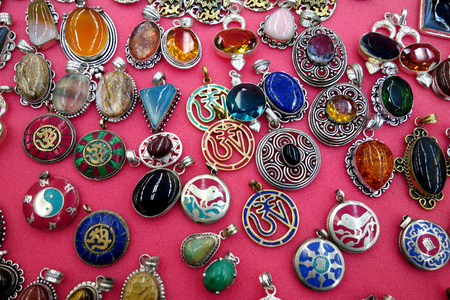 Indian collection of pendants and pins on a red                     Stock Photo - 22438275