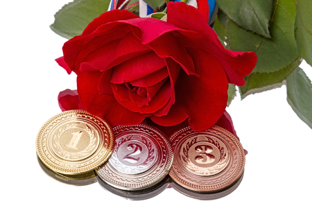 Sports Medal and a red rose  Isolated on white background photo