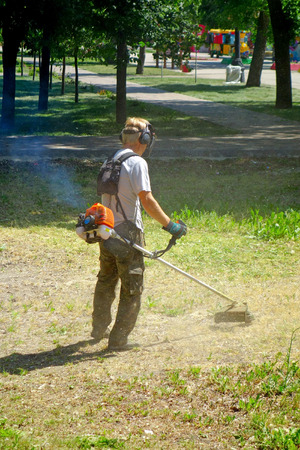 identified: Male hand gasoline mower mows the lawn. Man can not be identified Stock Photo