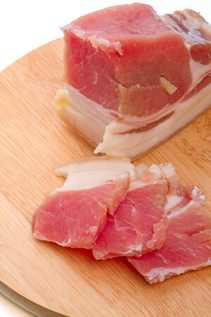 uncooked bacon: Salty bacon with garlic on a cutting board  Stock Photo
