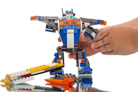 탐 보프, 러시아 - 2014 년 8 월 16 일 : 아이 빌드 레고 - 로봇 흰색 배경에. 레고 (Lego)는 덴마크 빌룬 드 (Billund)에 소재한 비상장 회사 인 레고 그룹 (Lego Gr 에디토리얼
