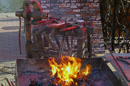forge: Fire in the forge and working tools on the river bank Stock Photo