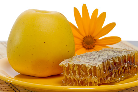 apple and honey: Yellow apple, honey in the comb and orange daisy on white Stock Photo