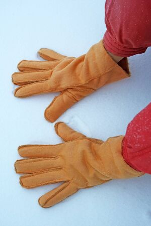 gloved: Hands with warm gloves on the first snow Stock Photo
