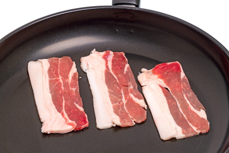 uncooked bacon: Three slices of bacon in a frying pan