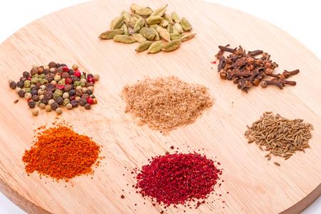 sumy: Seven spices (pepper, adjika, Sumy, cardamom, Zira, cinnamon, salt and herbs) on a round cutting board.