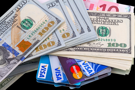 credit union: Tambov, Russian Federation - May 25, 2014: Background of cash (dollars and euros) and credit cards (Visa and Mastercard). Visa and Mastercard are a two biggest credit card companies in the world.