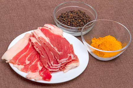 uncooked bacon: Pieces of bacon and spices - pepper pots and turmeric